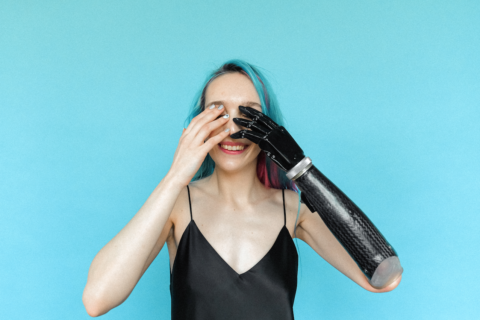 Woman with prosthetic arm covers her eyes in front of a blue wall