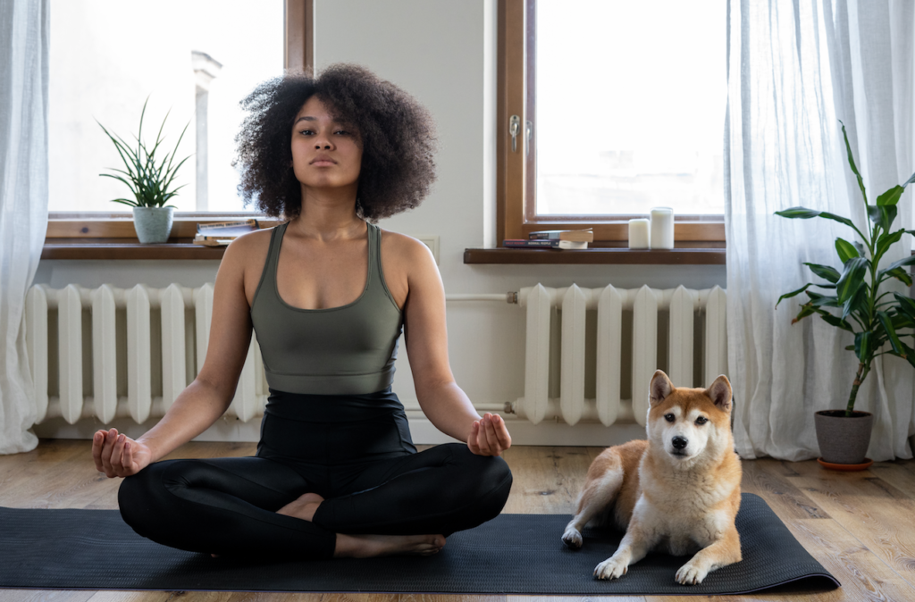 woman meditating next to her dog